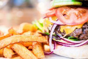 Nahaufnahme von Pommes und einem Burger aus der Bordküche von dem Restaurant am Flugplatz