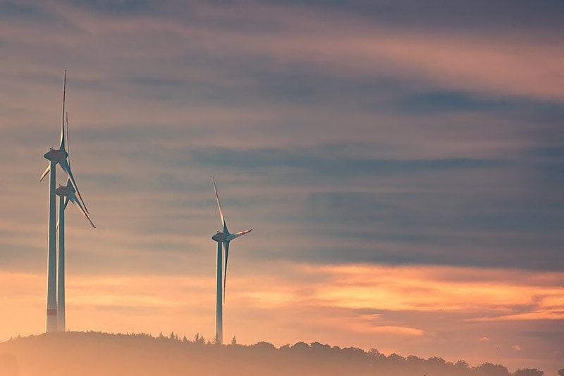 Landschaft mit drei Windrändern bei Sonnenuntergang