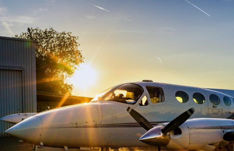 Nahaufnahme eines Flugzeugs, das vor einem Sonnenuntergang auf einer Landefläche steht
